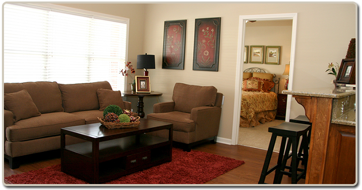 A picture taken of the living room and kitchen area in our 2 bedroom apartment model.